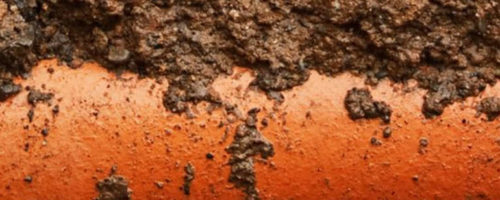 An orange pipe is buried under soil and under an asphalt street.
